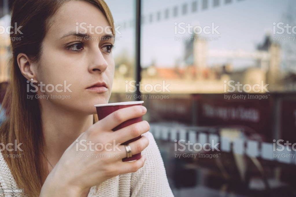 Thoughtful woman with coffee cup at building terrace in London stock photo
