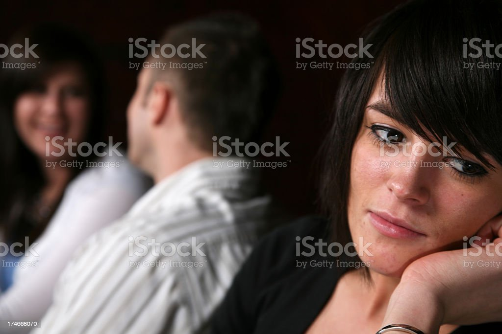 Thoughtful Woman with Couple Smiling Behind Her royalty-free stock photo