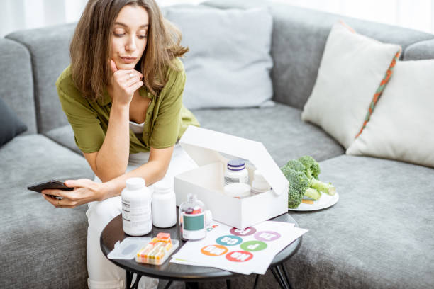 Thoughtful woman with vitamins or nutritional supplements at home Thoughtful woman with nutritional supplements at home. Concept of individual online selection of food supplements and preventive medicine biohacking stock pictures, royalty-free photos & images