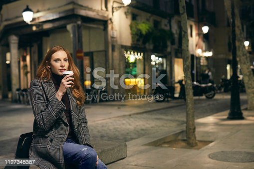 Thoughtful women having coffee while sitting on bench. Beautiful female is in warm clothing. She is in city at night.