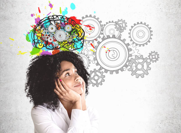 Thoughtful young African woman brainstorming Smiling young African American woman in white shirt looking at colorful brain sketch with gears drawn on concrete wall. Concept of brainstorming reflection stock pictures, royalty-free photos & images