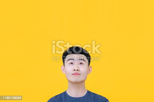 istock Thoughtful young Asian man looking up to copy space 1185126055