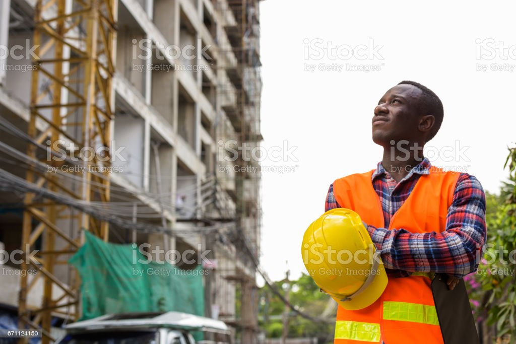 Thoughtful young black African man construction worker holding clipboard and hard hat with arms crossed at building site stock photo