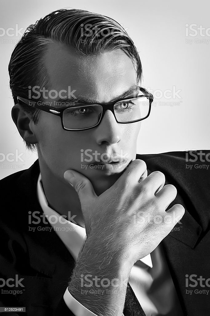 Thoughtful young businessman. Handsome blonde man with glasses stock photo