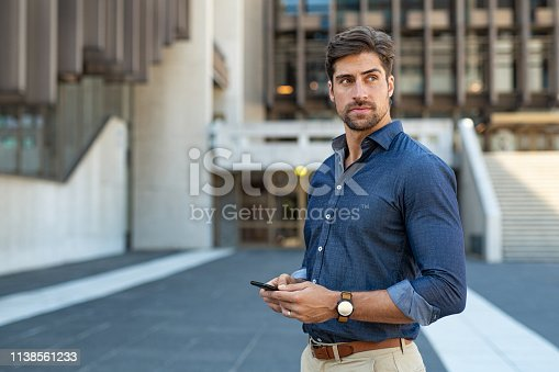 Smart casual man using smartphone outdoor. Portrait of young businessman using mobile phone while looking away on the street. Thoughtful business man in blue formal clothing using cellphone outside office building.