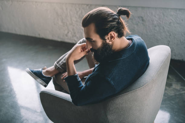 thoughtful young businessman thoughtful young businessman sitting in armchair man bun stock pictures, royalty-free photos & images