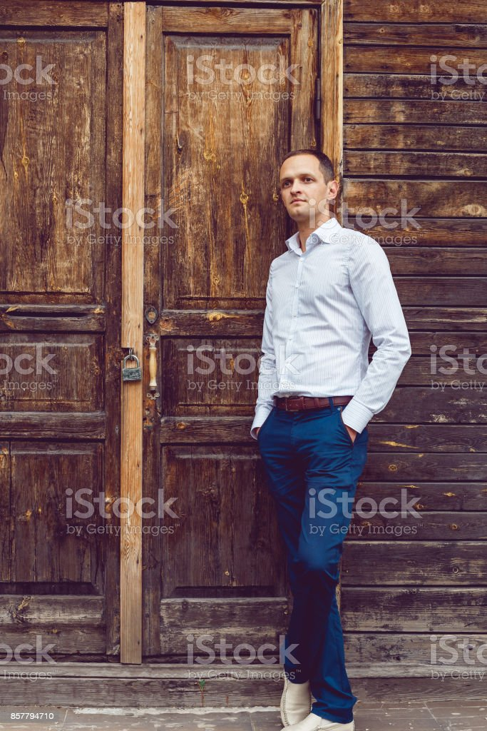 A thoughtful young businessman stands near a wooden wall stock photo