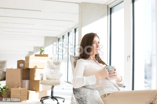 istock Thoughtful young businesswoman having coffee in new office 613870354