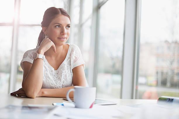 Aufmerksamen junge Geschäftsfrau sitzt am Schreibtisch – Foto