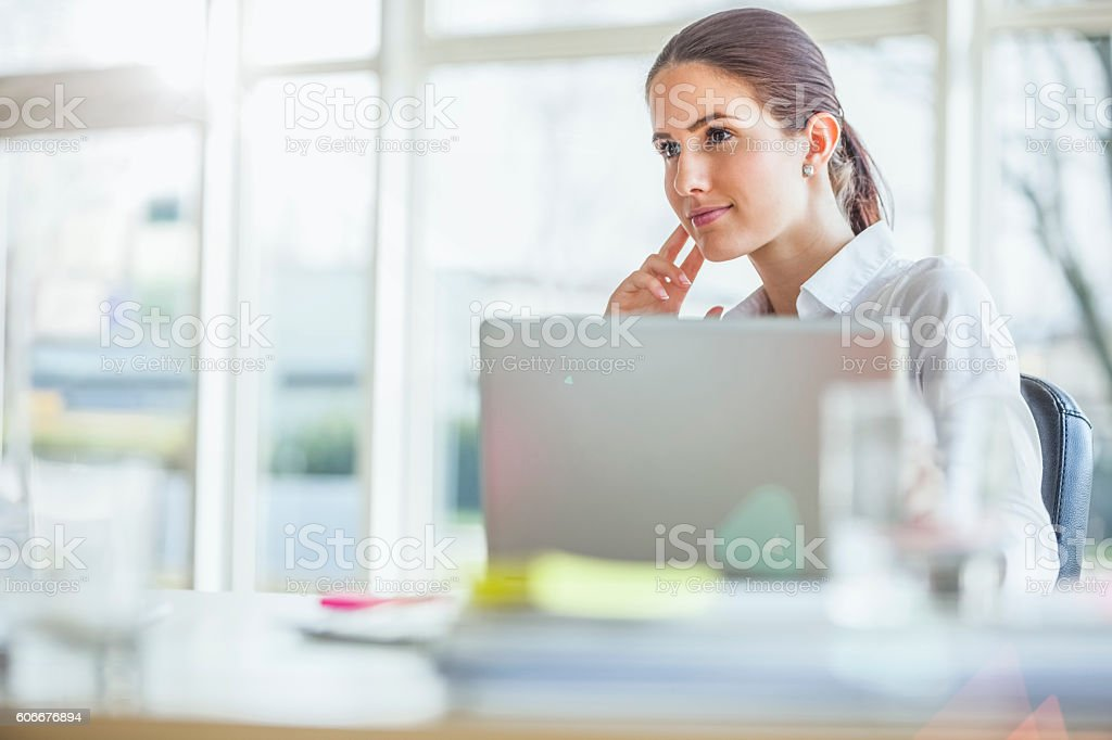 Thoughtful young businesswoman sitting at office desk stock photo