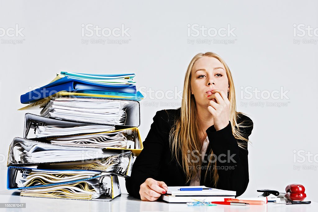 Thoughtful young businesswoman with enormous workload royalty-free stock photo