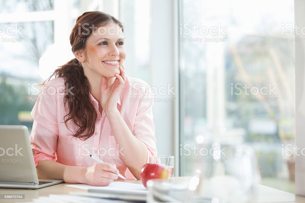 Thoughtful young businesswoman writing on document at office desk stock photo