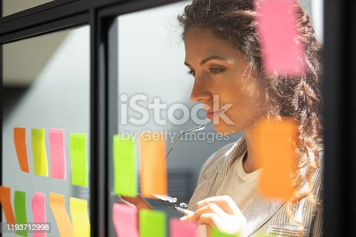 1144569896 istock photo Thoughtful young female boss team leader looking at kanban board. 1193712998