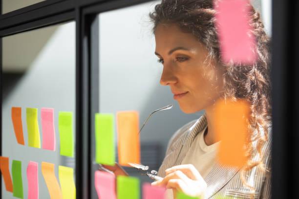 thoughtful young female boss team leader looking at kanban board. - agilidade imagens e fotografias de stock
