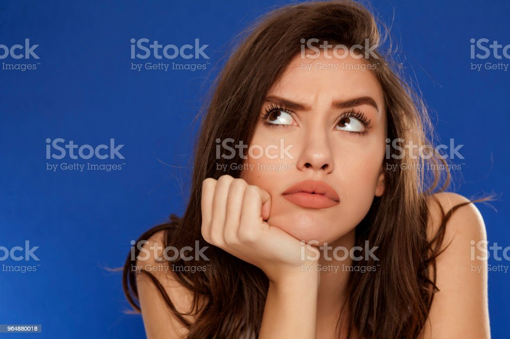 thoughtful young frowning woman on blue background royalty-free stock photo