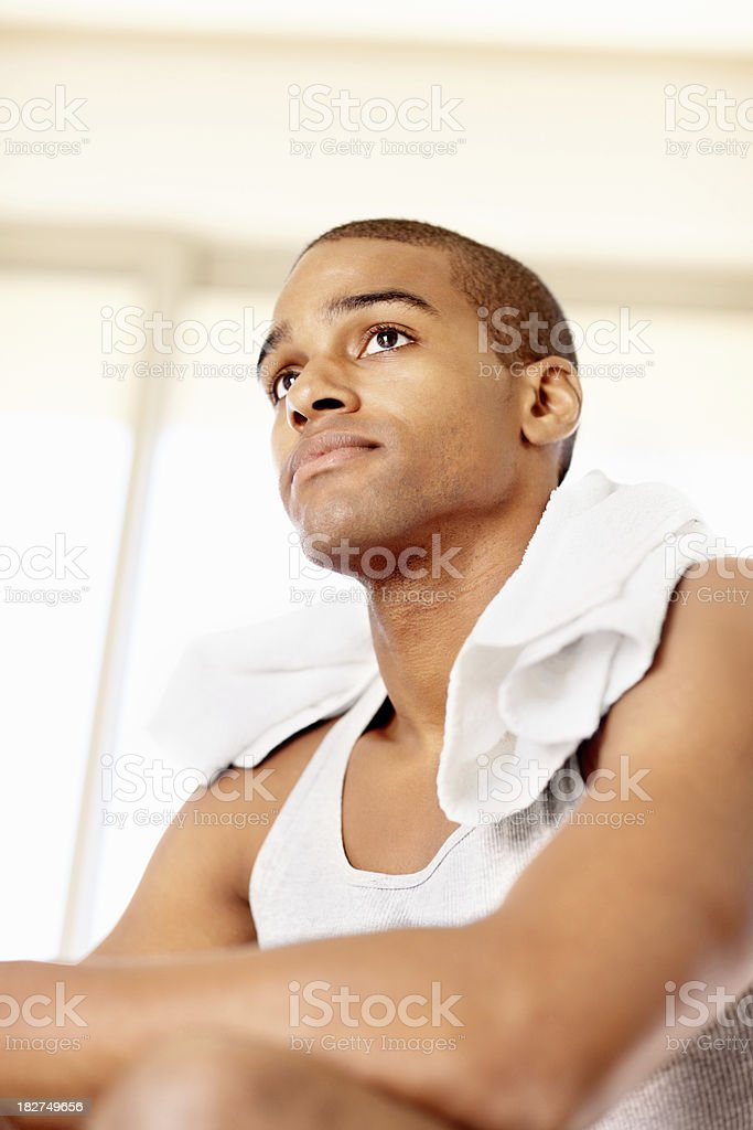 Thoughtful young guy with towel around the neck royalty-free stock photo