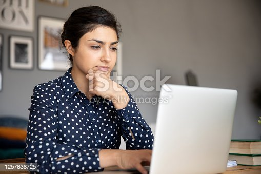 Head shot thoughtful young indian woman looking at computer screen. Focused millennial female college university student doing homework. Concentrated freelancer working remotely online at home.