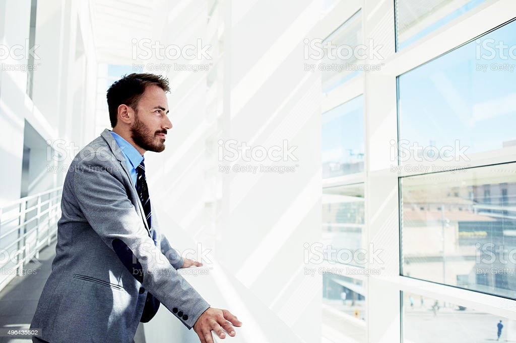 Thoughtful young male entrepreneur in suit resting after business meeting Portrait of a serious man office worker dressed in elegant clothes watching in window while standing in modern office space, 2015 Stock Photo