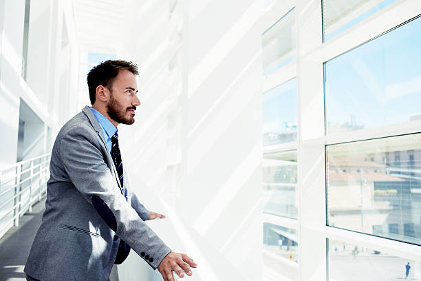 Thoughtful young male entrepreneur in suit resting after business meeting stock photo