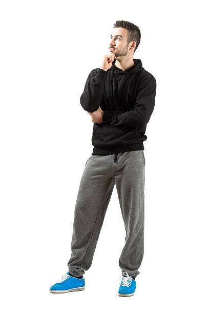 nachdenklicher junger mann in-hoodie - sweatpants stock-fotos und bilder