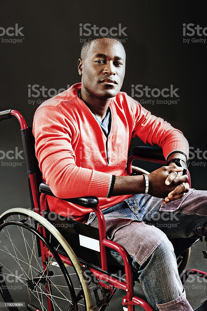Thoughtful young man in wheelchair considers his options royalty-free stock photo