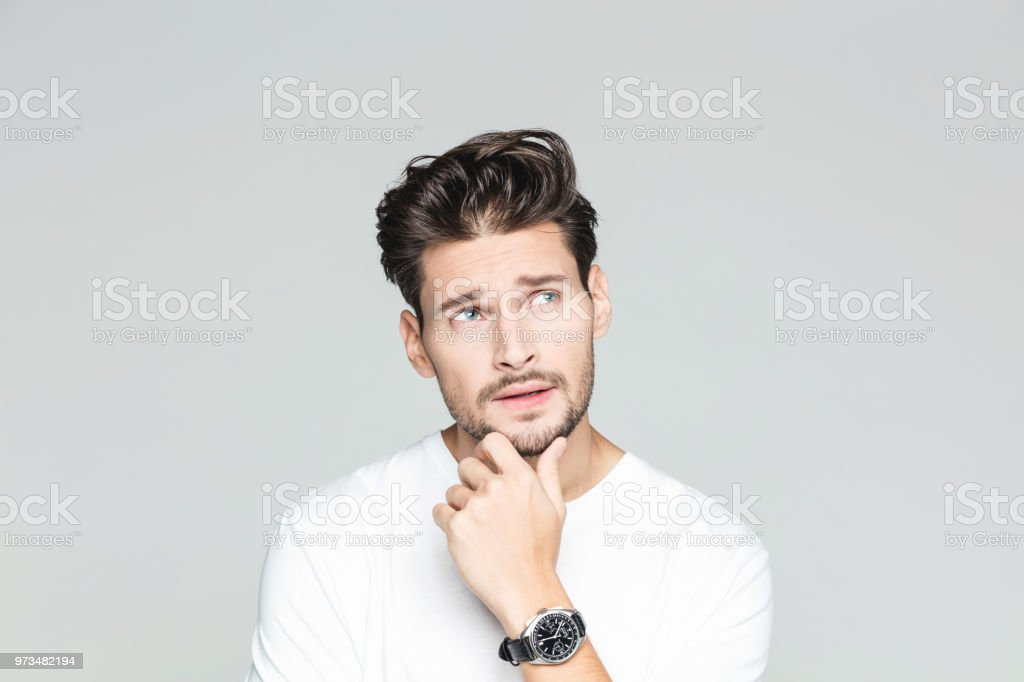 Thoughtful young man Portrait of handsome young man looking away and thinking against grey background 25-29 Years Stock Photo