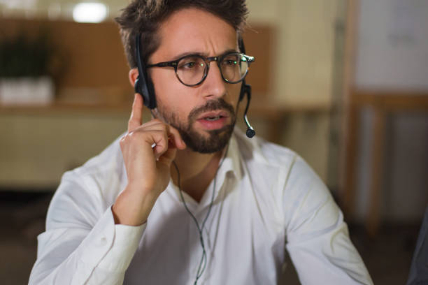 Thoughtful young man receiving incoming call stock photo