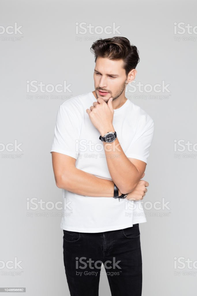 Thoughtful young man standing on grey background Portrait of thoughtful young man standing on grey background and looking away 25-29 Years Stock Photo