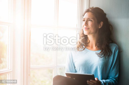 A photo of thoughtful woman sitting on window sill. Young female is holding digital tablet while looking away. She is wearing casuals in brightly lit room.