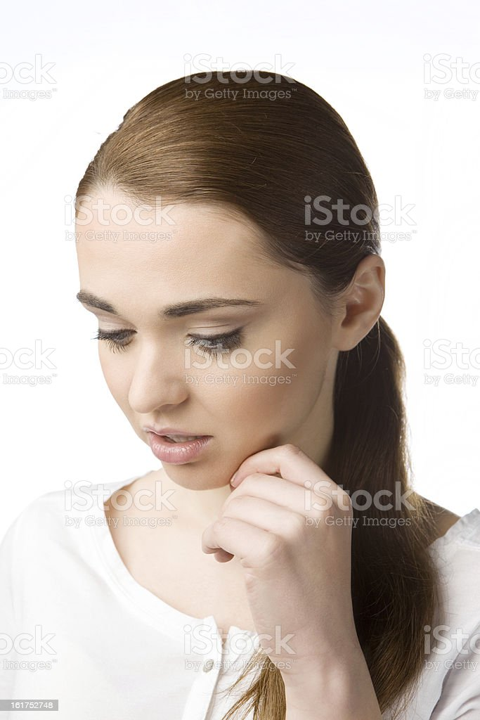 Thoughtful young woman holding her hand at chin, staring down stock photo
