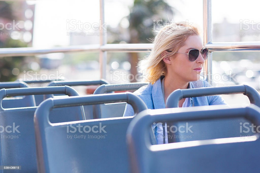 thoughtful young woman on open top bus stock photo