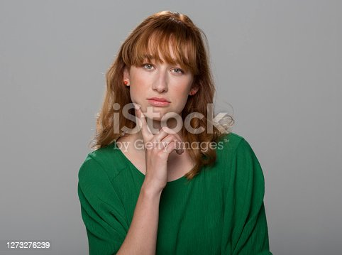 Portrait of thoughtful young woman standing against grey background.