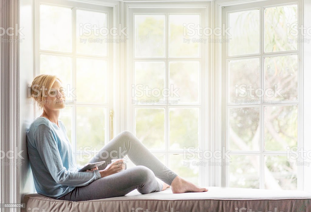 Thoughtful young woman relaxing on window sill stock photo