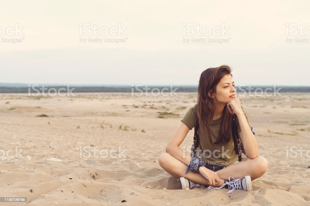 Thoughtful young woman sitting on sand in desert Full length of thoughtful young woman sitting on sand. Beautiful female is relaxing in desert after hiking. She is wearing casuals. 25-29 Years Stock Photo
