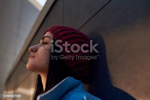 istock Thoughtful young woman standing close to a wall 1239597105