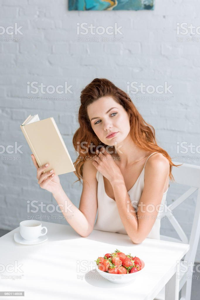thoughtful young woman with book and cup of coffee sitting at table stock photo