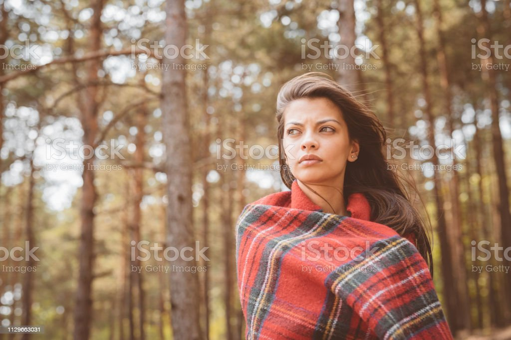 Thoughtful young woman wrapped in red blanket Thoughtful young woman wrapped in red blanket against trees. Beautiful female is looking away. Hipster is spending vacation in forest. 25-29 Years Stock Photo