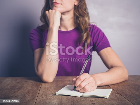 istock Thoughtful young woman writing in notepad 499335554