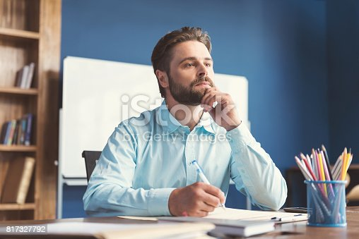istock Thoughtful youthful bearded guy doing test for job employment 817327792