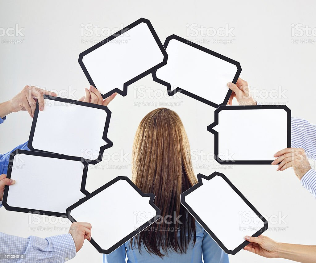 Thoughts Back view of businesswoman surrounded by many speech bubbles with copyspace. Adult Stock Photo