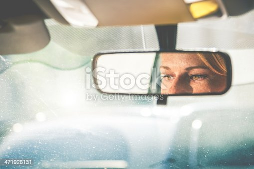 Blonde woman driving the car in the city traffic.