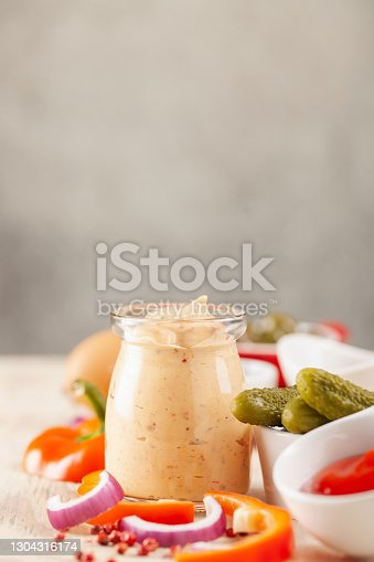 istock Thousand Islands sauce and ingredients - cucumbers, onions, paprika, ketchup and mayonnaise in bowls on the table. American cuisine, dip for burgers and meat. 1304316174