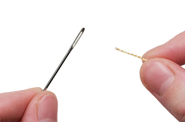 A thread being steadied through the eyelet of a needle stock photo