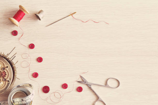 thread, needle, scissors and buttons - basic accessories starting sewing. sewing works. handmade. womanly hobby. - sewing machine needle stock photos and pictures