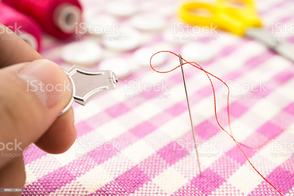thread pass the hole of sewing needle with threader stock photo