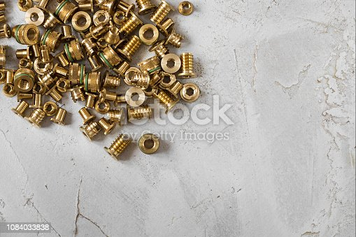 Many metal gold threaded inserts made of lattin metal for making very hard connection between plastic details, oblong horizontal shot made from top view on the background of grey cement rustic surface