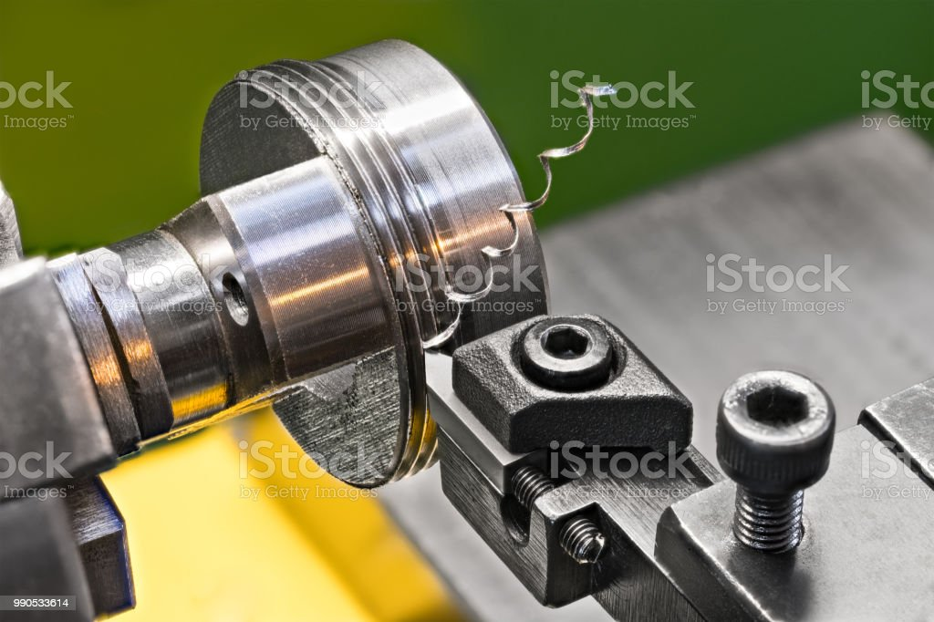 Threading by a steel tool bit on a lathe.  Idea of machining and metalwork stock photo