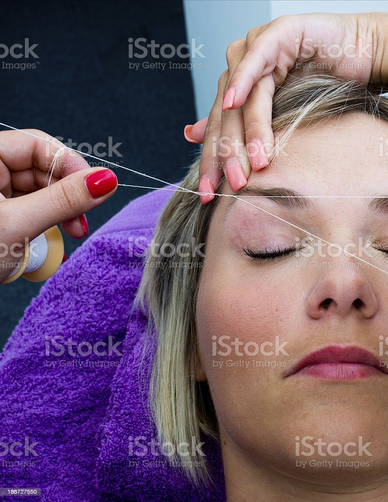 threading hair removal procedure stock photo