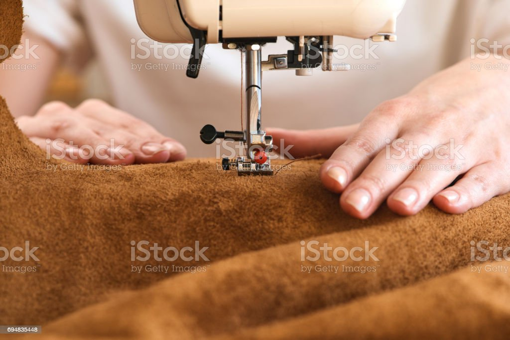 Threading leather on sewing machine stock photo