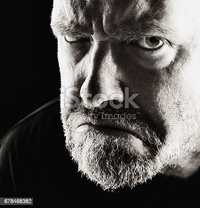 A middle-aged man frowns and scowls at camera in a very menacing way in this stark black and white portrait.